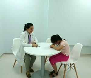 Hình chuyên gia tâm lý đang thực hiện bài kiểm tra bằng cách yêu cầu trẻ vẽ ra những hình ảnh trẻ quan tâm (Hình ảnh đã được sự đồng ý của phụ huynh)