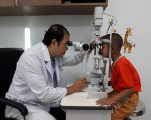 Bác sĩ chuyên gia đang thăm khám mắt cho bé bằng sinh hiển vi.