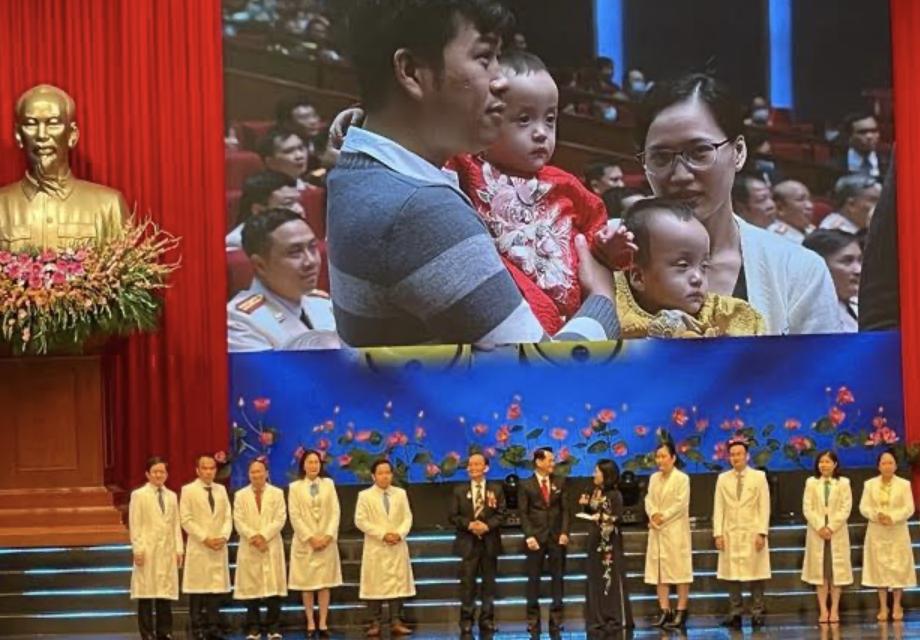 Hình ảnh cặp song sinh dính Trúc Nhi – Diệu Nhi trước và sau mỗ cùng với bố, mẹ xuất hiện tại Trung tâm Hội nghị Quốc gia và được hơn 2.000 đại biểu vỗ tay chúc mừng